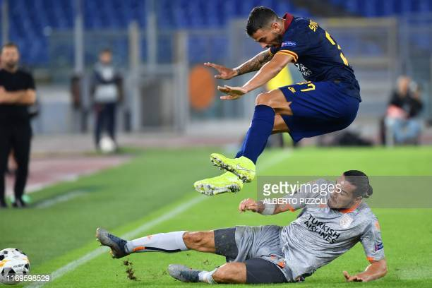 Roma's Italian defender Leonardo Spinazzola jumps above Istanbul Basaksehir FK's French forward Enzo Crivelli during the UEFA Europa League Group J...