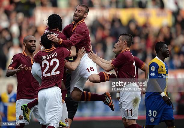 AS Roma's Italian forward Francesco Totti is congratulated by teammates Maicon Mattia Destro Gervinho Daniele De Rossi and Taddei after scoring...
