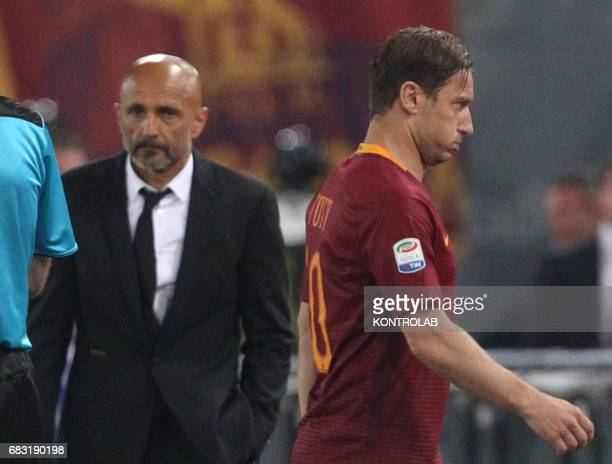 Roma's Italian forward Francesco Totti leave the pitch as pass Roma's Italian coach Luciano Spalletti during the Italian Serie A football match AS...