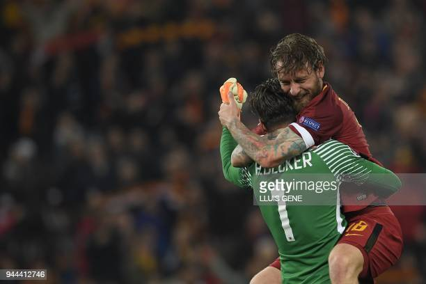 AS Roma's Italian midfielder Daniele De Rossi and AS Roma's Brazilian goalkeeper Alisson Becker celebrate after winning the UEFA Champions League...