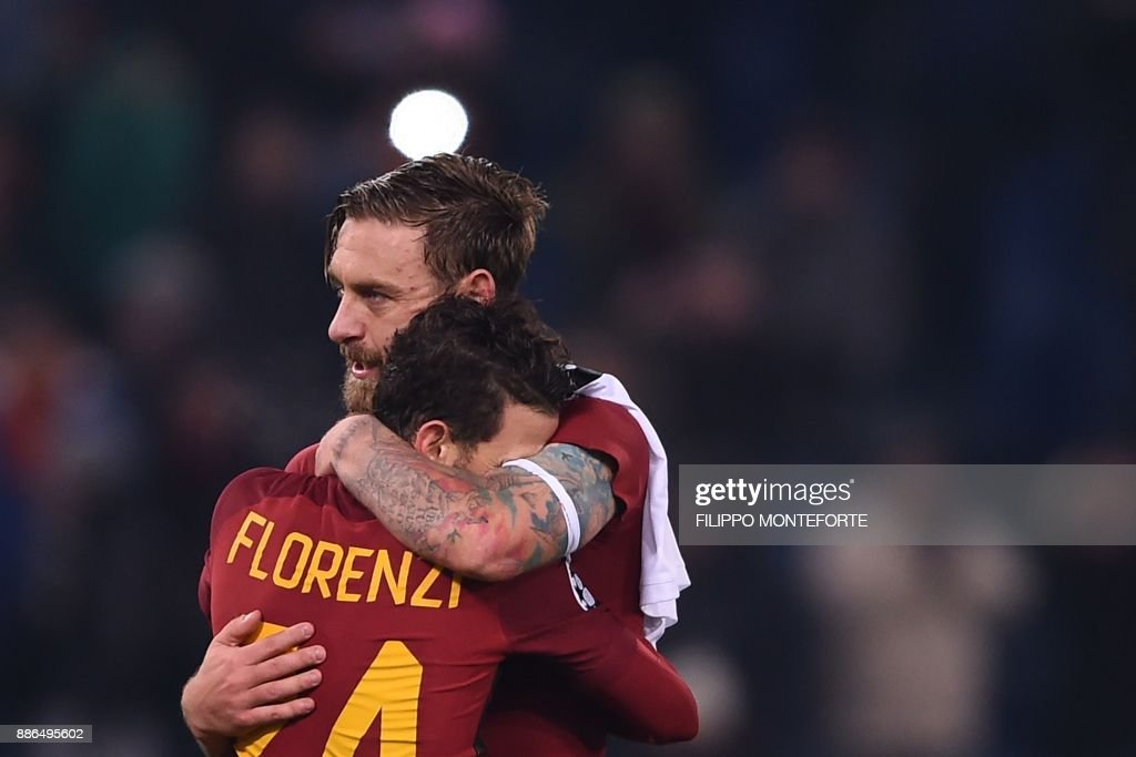 Roma's Italian midfielder Daniele De Rossi celebrates with Roma's Italian midfielder Alessandro Florenzi at the end of the UEFA Champions League Group C football match AS Roma vs FK Qarabag on December 5, 2017 at the Olympic stadium in Rome. Roma won 1-0 and reach Champions League last 16. / AFP PHOTO / Filippo MONTEFORTE