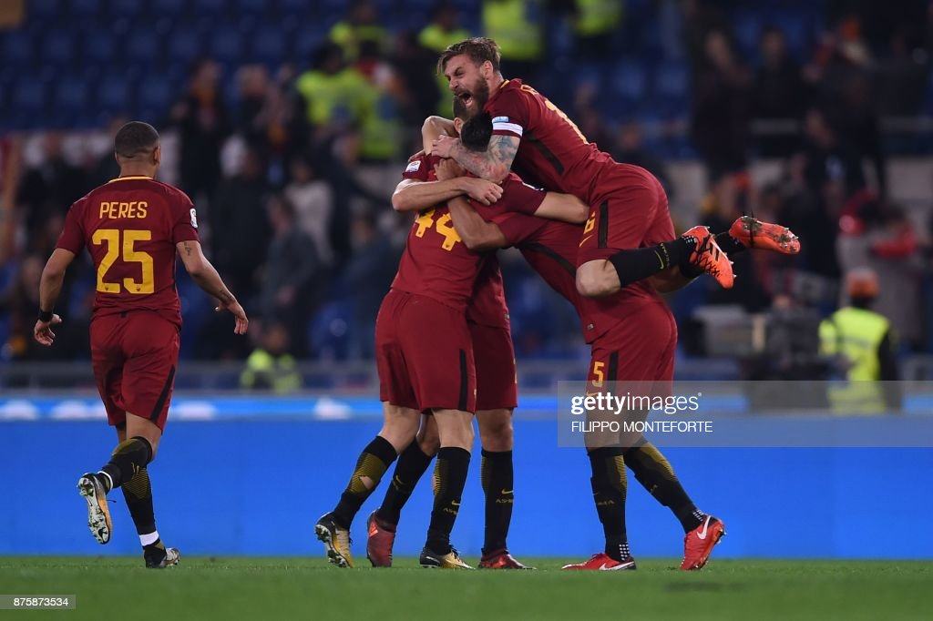 Roma's Italian midfielder Daniele De Rossi (top) celebrates with teammates at the end of the Italian Serie A football match AS Roma vs Lazio on November 18, 2017 at the Olympic stadium in Rome. AS Roma won 2-1. / AFP PHOTO / Filippo MONTEFORTE