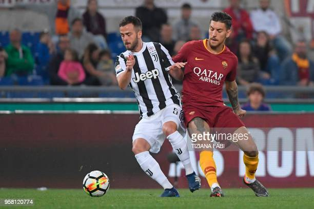 Roma's Italian midfielder Lorenzo Pellegrini vies with Juventus midfielder from Italy Miralem Pjanic during the Italian Serie A football match AS...