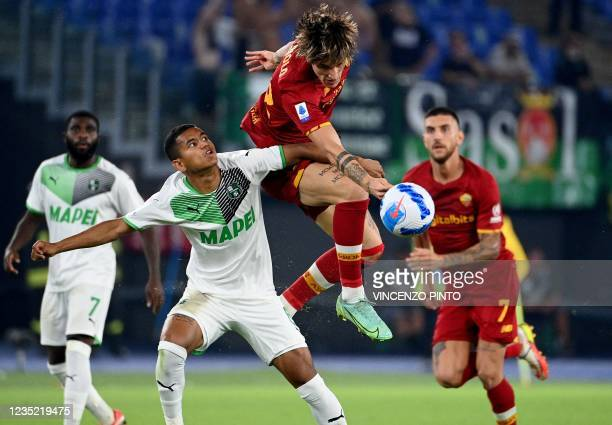 Roma's Italy's midfielder Nicolo Zaniolo fights for the ball with Sassuolo's Brazil's defender Rogerio during the Italian Serie A football match...