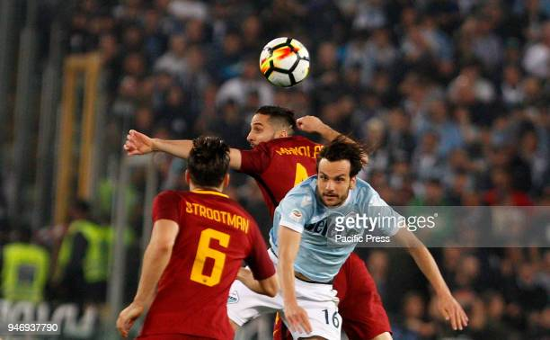 Roma's Kostas Manolas center and Lazio's Marco Parolo jump for the ball during the Serie A soccer match between Lazio and Roma at the Olympic stadium