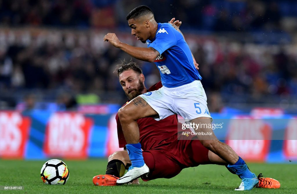 Roma's midfielder Daniele De Rossi (L) fights for the ball with Napoli's Brazilian midfielder Allan during the Italian Serie A football match Roma vs Napoli at the Olympic Stadium in Rome on October 14, 2017. /