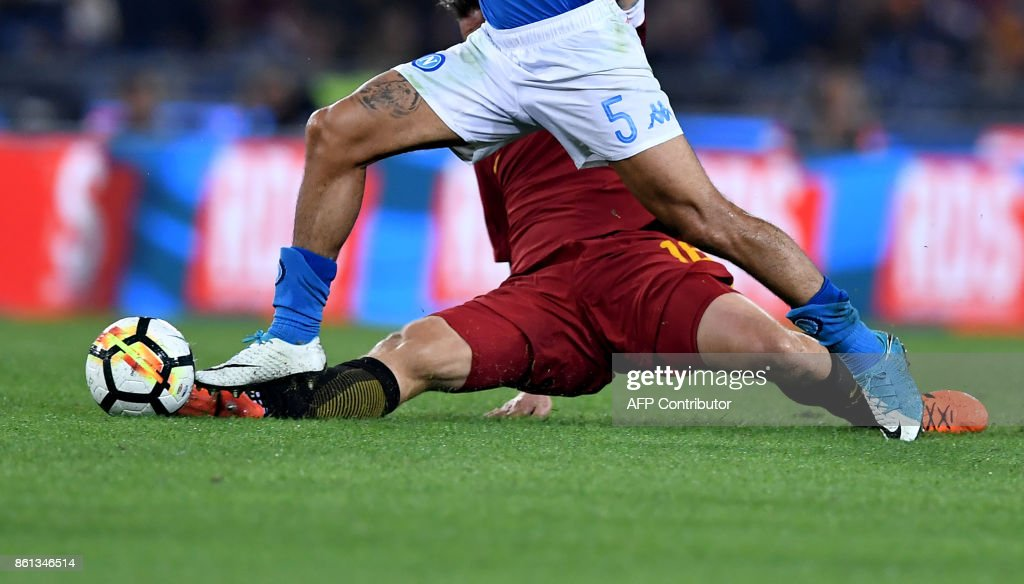 Roma's midfielder Daniele De Rossi (bottom) fights for the ball with Napoli's Brazilian midfielder Allan during the Italian Serie A football match Roma vs Napoli at the Olympic Stadium in Rome on October 14, 2017. /