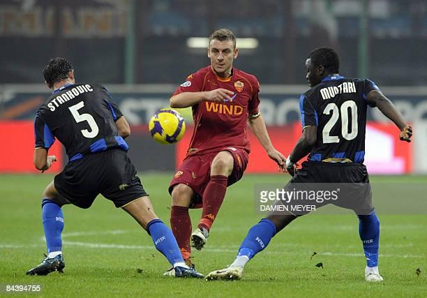 Roma's midfielder Daniele De Rossi kicks the ball as he is framed by Inter Milan's Serbian midfielder Dejan Stankovic and teammate Ghanaian...