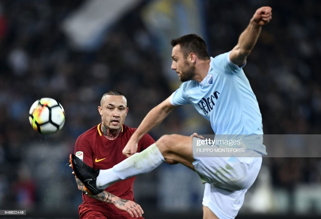 Roma's midfielder from Belgium Radja Nainggolan (L) vies for the ball with Lazio's defender from the Netherlands Stefan de Vrij during the Italian Serie A football match between Lazio and Roma on April 15, 2018 at Olympic Stadium in Rome. /