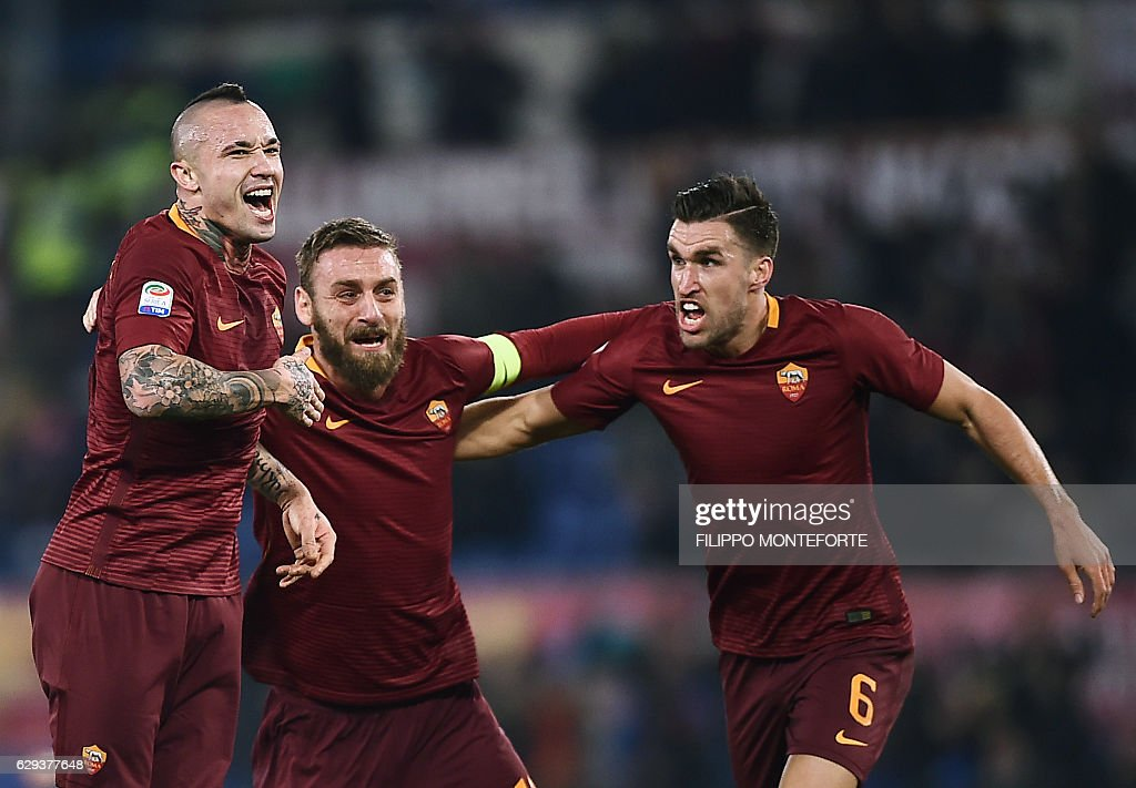 Roma's midfielder from Belgium Radja Nianggolan (C) celebrates with teammates after scoring during the Italian Serie A football match Roma vs AC Milan at the Olympic Stadium in Roma on December 12, 2016. / AFP / FILIPPO