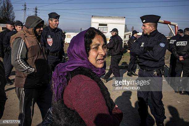 Romas people stand next to policemen after being evicted from their makeshift camp on March 5 2014 in Lyon AFP PHOTO / JEFF PACHOUD