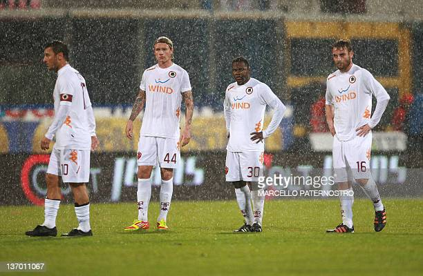 Roma's players react as a referee suspends an Italian Serie A football match against Catania due to heavy rain on January 14, 2012 at the Massimino...