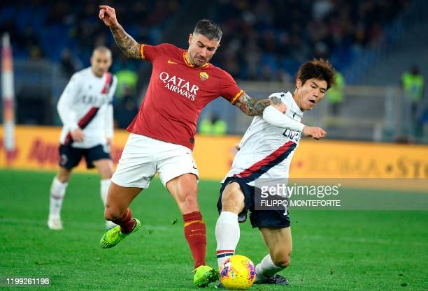 AS Roma's Serbian defender Aleksandar Kolarov is tackled by Bologna's Japanese defender Takehiro Tomiyasu during the Italian Serie A football match...