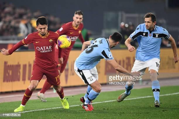AS Roma's Turkish forward Cengiz Under challenges Lazio's Romanian defender Stefan Radu as Lazio's Bosnian midfielder Senad Lulic looks on during the...