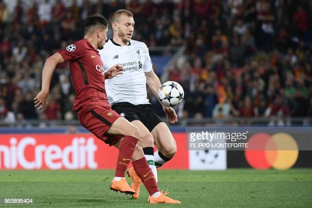 Roma's Turkish midfielder Cengiz Under challenges Liverpool's Estonian defender Ragnar Klavan who touches the ball with his hand in the penalty area...