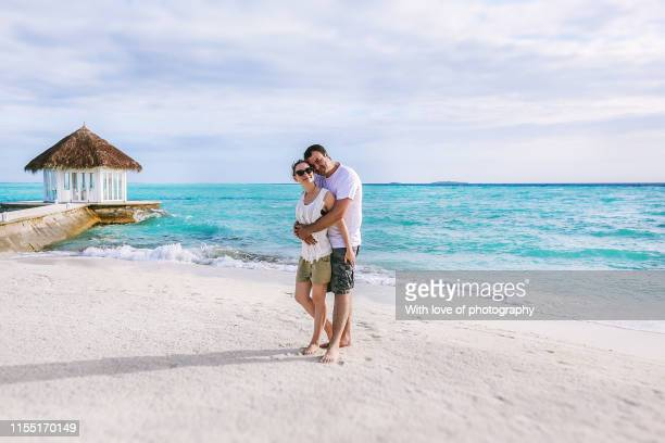 romasntic couple in maldives walking on the beach hugging and cuddling, love and romance, romantic getaway, honeymoon, loving couple, romance in maldives, love and ocean, just for two, ocean waves, island vibes, romantic holiday, caucasian happy couple in - love island stock pictures, royalty-free photos & images