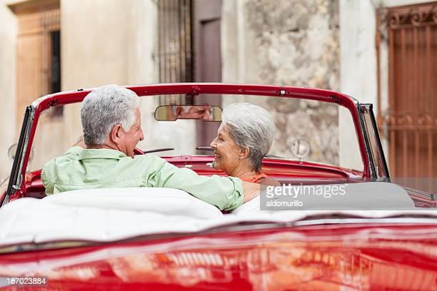Romatic senior couple driving in Cuba