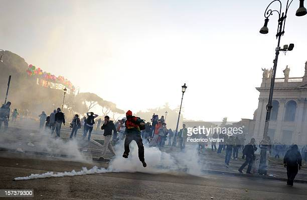 Rome 15 October 2011 Protesters kick back a tear gas canister towards riot police in Piazza San Giovanni