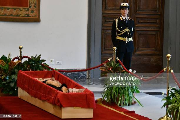 A Rome city police officer stands by the open coffin where Italian film director Bernardo Bertolucci lies in state in a chapel of rest at Rome's...
