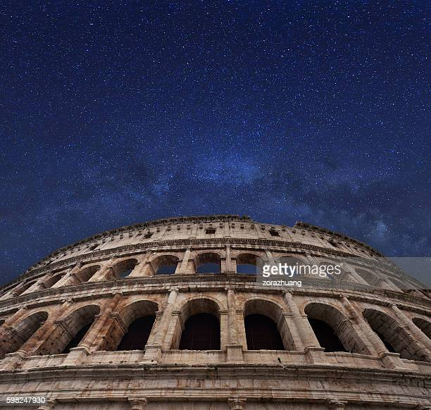 rome coliseum and milky way in the midnight sky - coliseum rome stock photos and pictures