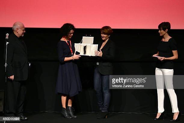 Rome Film Festival director Marco Mueller stands with Lenka Kabankova as she receives from a guest her Best Cinematography Studio Universal Award for...