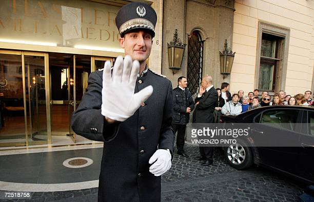 A doorman tries to stop fans of Hollywood superstar Tom Cruise waiting in front of a central Rome's hotel where Cruise and his fiancee Katie Holmes...