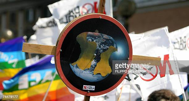 A protester holds a banner with an earth eaten during a demonstration against US President George W Bush planned by pacifist movements...