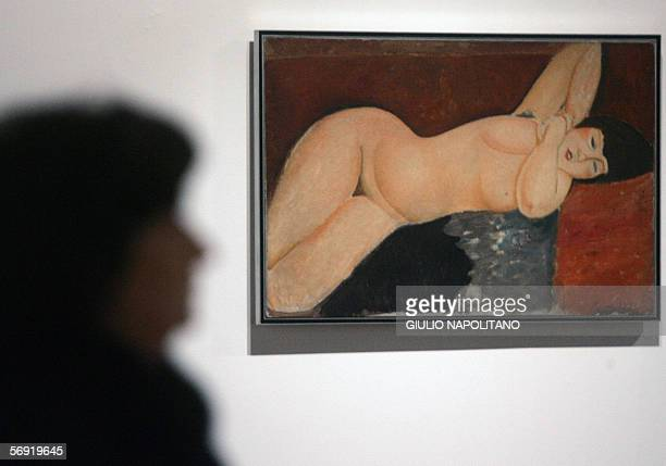 A woman looks at the painting 'Reclining nude with clasped hands' by Italian Amedeo Modigliani 23 February 2006 during the exhibition 'Modigliani' at...