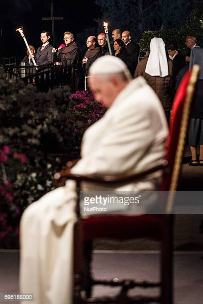 Faithful hold the cross during a station during the Via Crucis torchlight procession celebrated by Pope Francis in front of the Colosseum on Good...