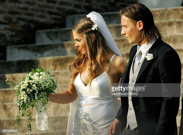 Roma captain Francesco Totti smiles to his wife Italian TV star Hilary Blasi leave the church after their wedding 19 June 2005 in Rome. AFP...