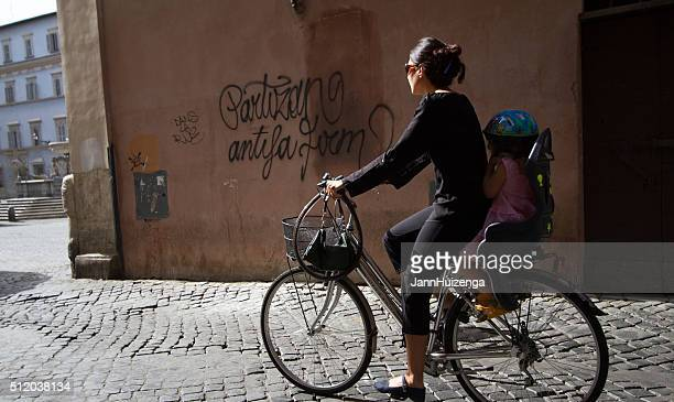 Rome, Italy: Early Morning Bicyclist and Child on Cobbled Street