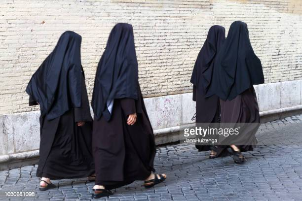 rome, italy: four nuns in black habits, trastevere - nun stock photos and pictures