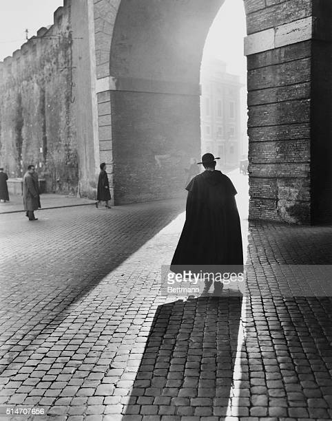 Rome Italy In pensive mood a young priest walks slowly toward an arch in Rome's St Peters Square making a dramatic picture of late afternoon...