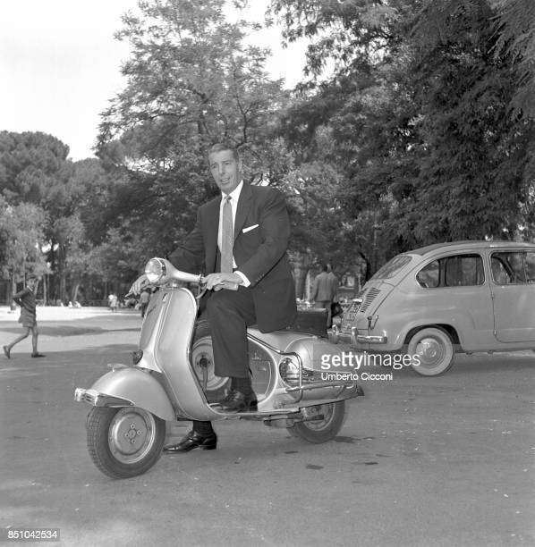 Rome Italy June 13 1957 Joe Di Maggio baseball champion and former husband of Marilyn Monroe rides a Vespa scooter a symbol of the Italian design...