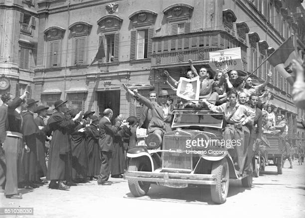 Rome, Italy, June 4, 1944. Catholic Partisans on a car applaud the Pope Pio XII waving the Italian flag with Savoy shield, forgetting that the...