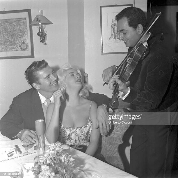 Rome Italy October 31 1959 Jayne Mansfield and her husband Mickey Hargitay surrender to gypsy melodies in the Roman restaurant 'Piccola Budapest'...