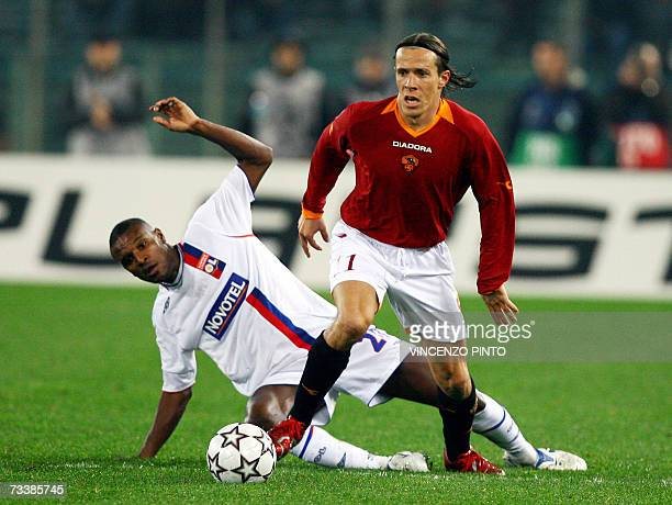 Rodrigo Taddei of AS Roma fights for the ball with Eric Abidal of Lyon during their first knockout round 1st leg at Rome's Olympic stadium 21...