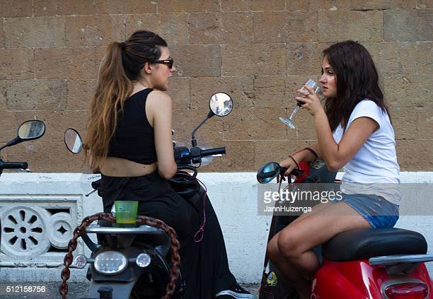 Rome, Italy: Young Women on Scooters with Drinks
