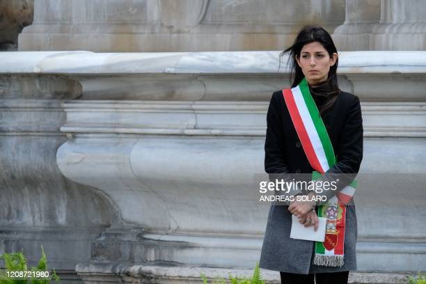 Rome mayor Virginia Raggi stands at attention during a minute of silence outside Rome's city hall at Capitoline Hill , on March 31, 2020 as flags are...
