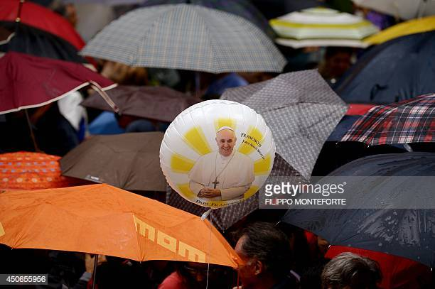 Rome residents one holding a balloon with a photo of Pope Francis protect themselves with umbrellas as they wait under the rain for the arrival of...