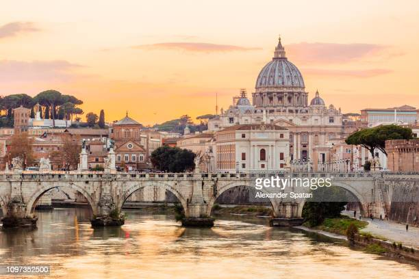 rome skyline at sunset with tiber river and st. peter's basilica, italy - rom italien stock-fotos und bilder