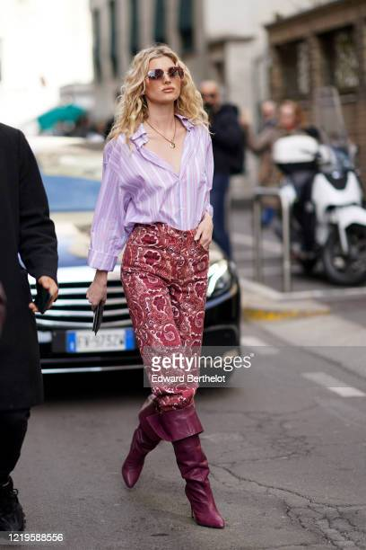 Romee Strijd wears a mauve pale purple shirt, a golden necklace, red pants with floral print, purple leather pointy boots, outside Etro, during Milan...