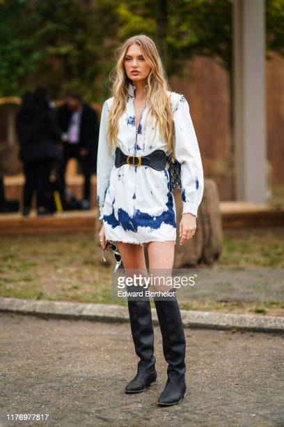 Romee Strijd wears a white dress with blue printed features black high boots outside Dior during Paris Fashion Week Womenswear Spring Summer 2020 on...