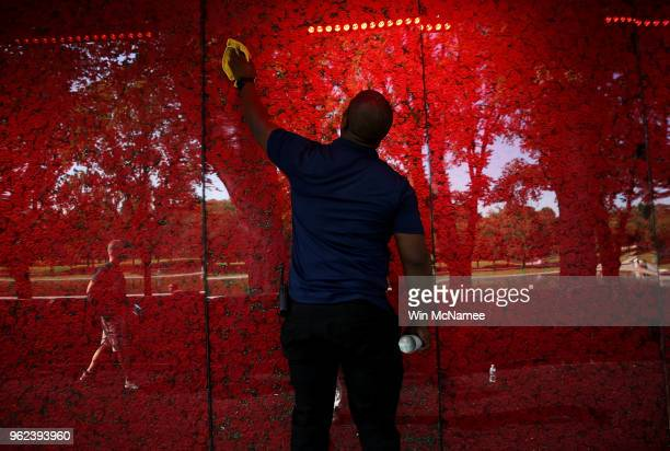 Romel Martin cleans glass panels while assisting with the installation of a temporary popup 'Poppy Memorial' on the national mall near the Lincoln...