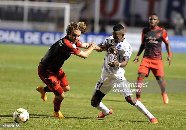 Romell Quioto of Honduras Olimpia vies for the ball with Michael Harrington of Portland Timbers from US during their CONCACAF Champions League at...