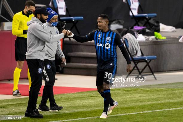 Romell Quioto of Montreal Impact gets a fist bump by head coach Thierry Henry after scoring the first goal of the Major League Soccer match against...