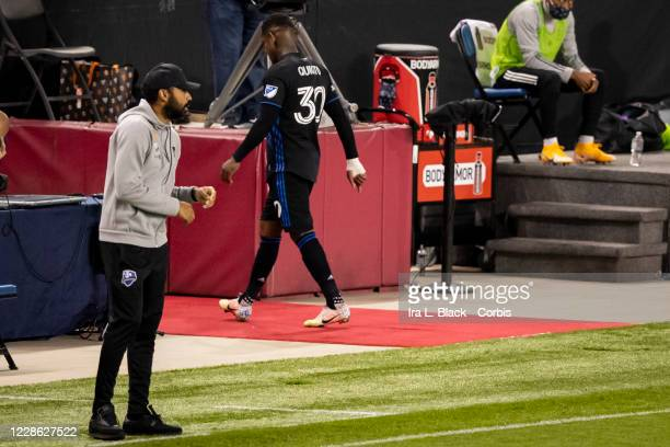 Romell Quioto of Montreal Impact walks off the pitch after receiving a red card while head coach Thierry Henry looks on during the first half of the...