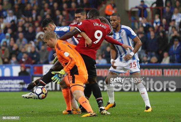 Romelu Lukaku of Manchester United is foiled by Jonas Lossl and Christopher Schindler of Huddersfield Town during the Premier League match between...
