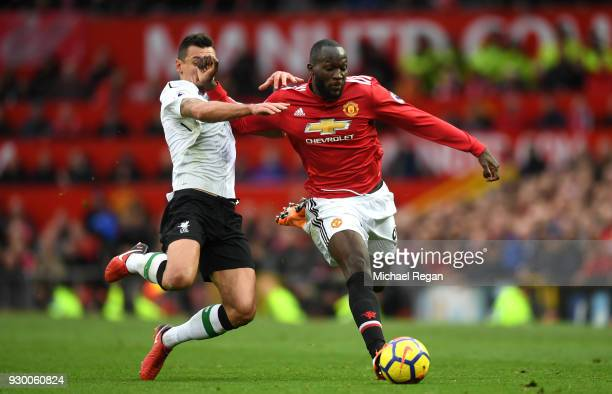 Romelu Lukaku of Manchester United runs with the ball under pressure from Dejan Lovren of Liverpool during the Premier League match between...