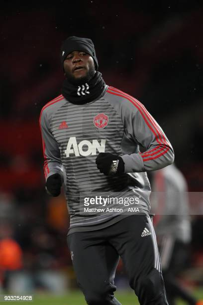 Romelu Lukaku of Manchester United wears a hat and snood in the cold weather whilst warming up during the FA Cup Quarter Final match between...